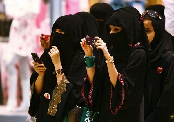 Veiled Saudi women take photos of their children during a ceremony to celebrate Saudi Arabia's Independence Day in Riyadh
